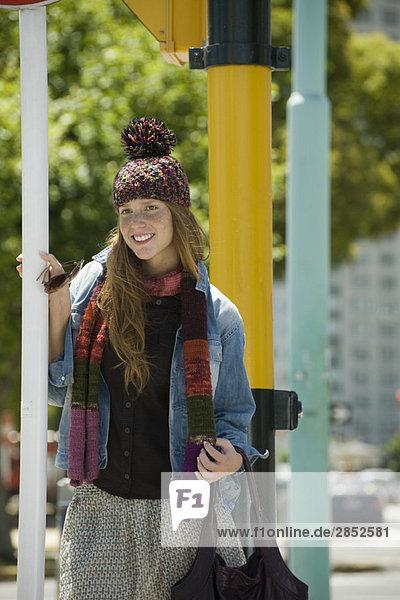 Junge Frau in trendiger Kleidung  lächelnd