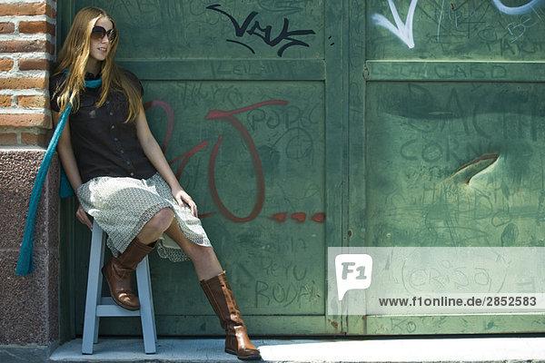 Trendige junge Frau sitzt auf Hocker vor graffitierter Wand