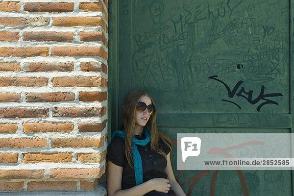 Junge Frau mit Sonnenbrille an der Wand lehnend