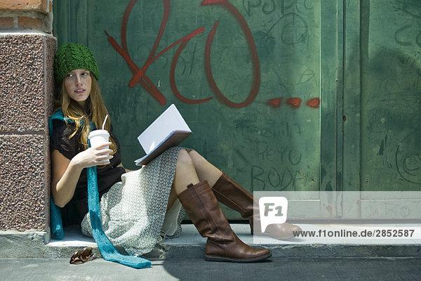 Junge Frau auf dem Boden sitzend mit Buch und Getränk  wegblickend