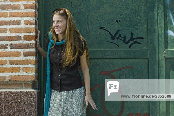 Junge Frau in der Gasse stehend  wegschauend  lächelnd