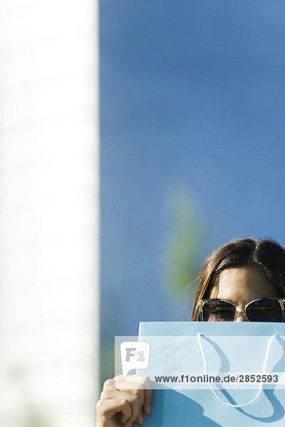 Junge Frau mit Sonnenbrille und Einkaufstasche vor dem Gesicht