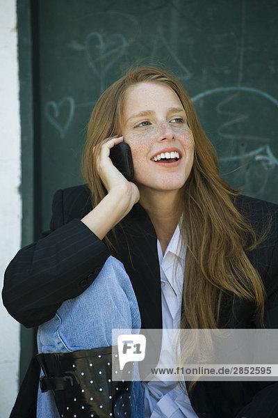 Junge Frau mit erdbeerblondem Haar und Sommersprossen  die am Handy spricht  lächelnd
