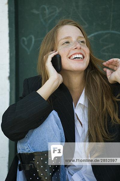 Junge Frau spricht am Handy  spielt mit den Haaren