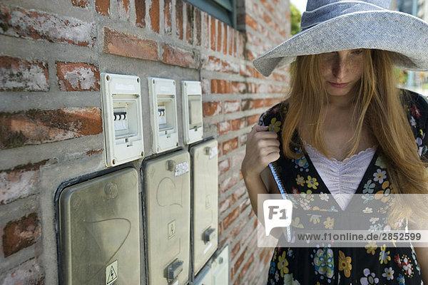 Junge Frau mit großem Hut und Blick nach unten.