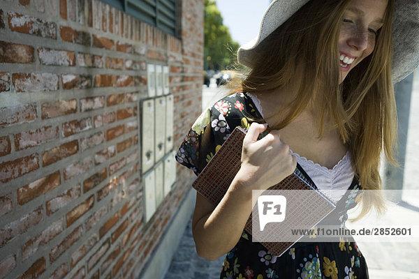 Junge Frau mit Notizbuch  lächelnd und herabblickend