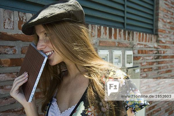 Junge Frau hält Notizbuch hoch  lächelnd  wegschauend