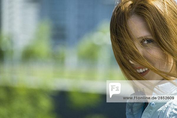 Junge rothaarige Frau mit über das Gesicht blasenden Haaren  Portrait