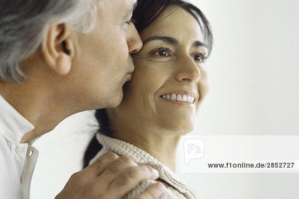 Reife Frau  Ehemann küsst ihre Wange von hinten.
