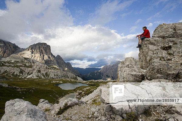Mann auf Berggipfel sitzend