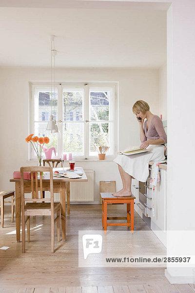 Frau in der Küche spricht am Telefon