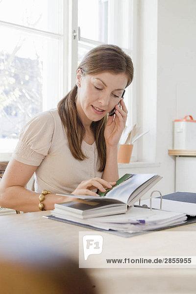 Frau am Tisch sitzend mit Telefon
