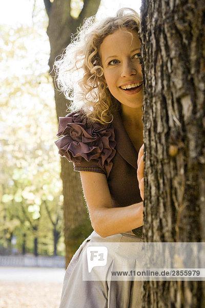 Frau versteckt sich hinter Baum