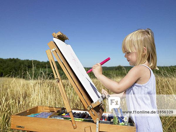 Mädchenmalerei auf einem Feld
