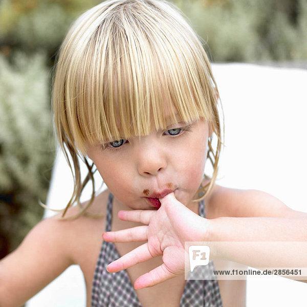 Mädchen leckt Schokolade am Finger Mädchen leckt Schokolade am Finger