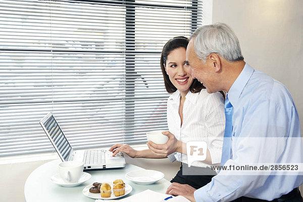 Mitarbeiter im Cafe mit lächelndem Laptop