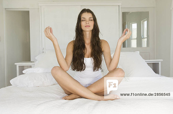 Female in yoga pose sitting on bed