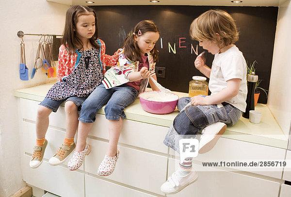 Zwei Mädchen und Jungen beim Kochen