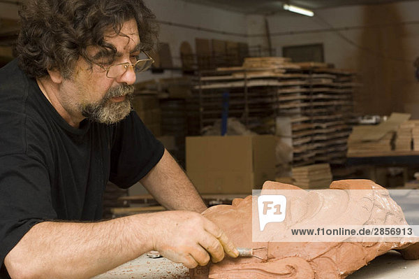 Man sculpting face in clay