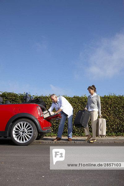 Reife Paare  die Taschen ins Auto packen