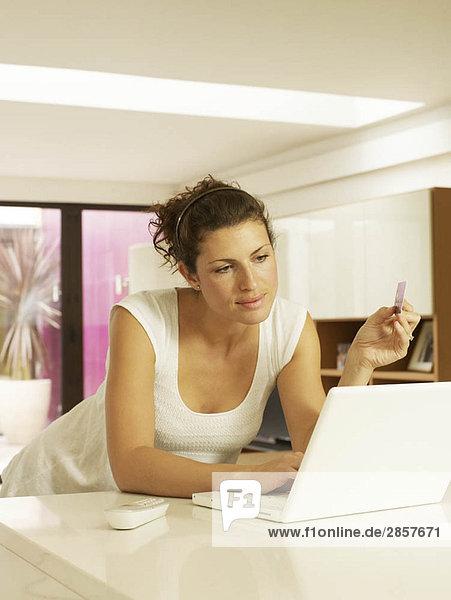 Frau mit Kreditkarte und Laptop