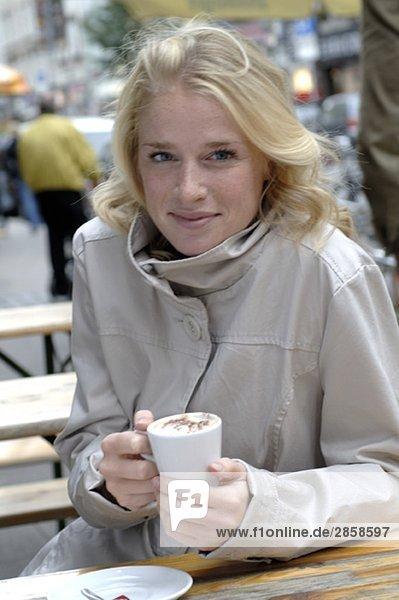 Blonde Frau hält Kaffeebecher in der Hand