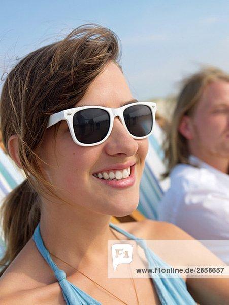 Beautiful young woman with sunglasses taking a sunbath