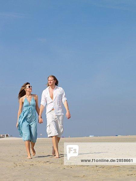 Paar spaziert hand in hand am Strand entlang