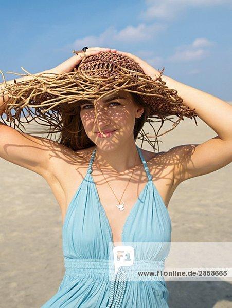 Junge Frau in hellblauem Sommerkleid und Strohhut am Strand