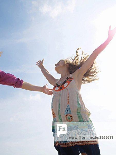 Junge Frau hüpft und springt am Strand