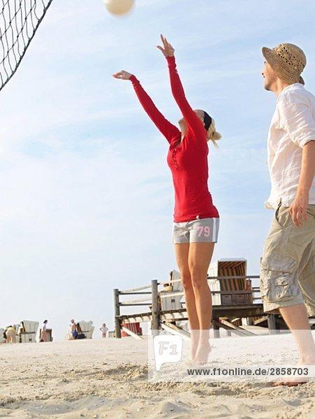 Junge Leute spielen Beachvolleyball
