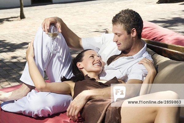 Young couple lying outdoors  man holding wine glass