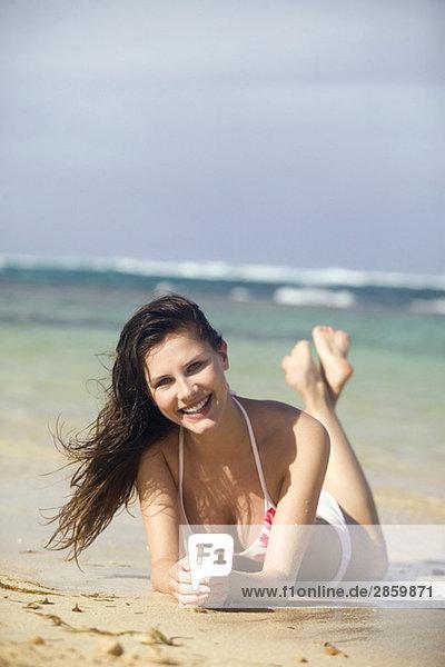 Junge Frau am Strand liegend  lächelnd  Portrait