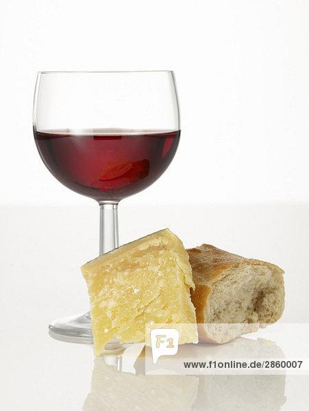 Parmesankäse  ein Glas Rotwein und ein Stück Weißbrot Parmesankäse, ein Glas Rotwein und ein Stück Weißbrot