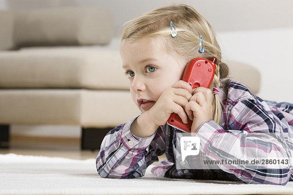 Kleines Mädchen (3-4) mit Spielzeugtelefon