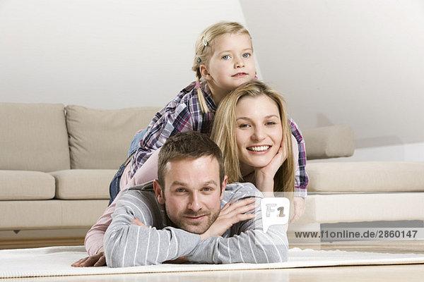 Eltern und Tochter (3-4) entspannt zu Hause