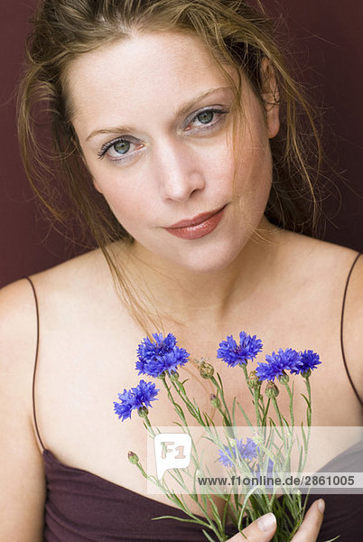 Young woman holding cornflowers  portrait  close up