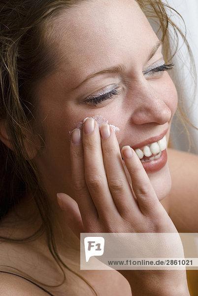 Junge Frau beim Auftragen der Hautcreme  Nahaufnahme