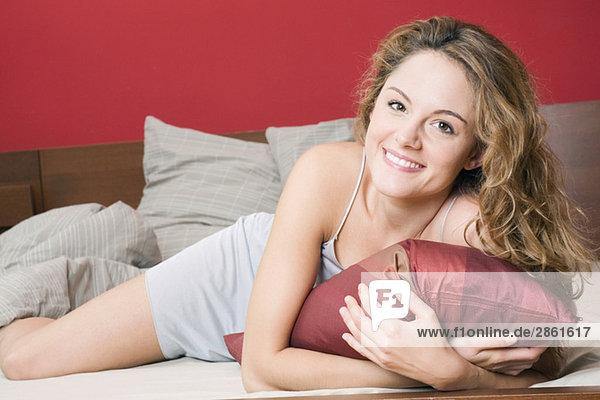 Junge Frau auf dem Bett liegend  lächelnd  Portrait