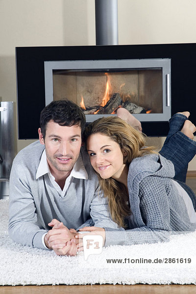 Junges Paar auf Teppich liegend  vor dem Kamin  lächelnd