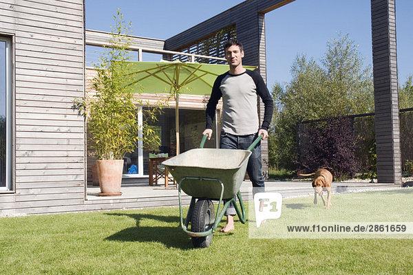man in garden  pushing wheel barrow