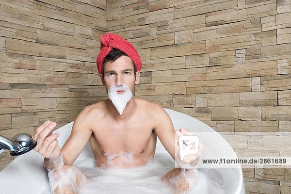 Young man wearing turban in bathtub