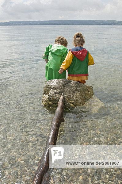 Deutschland  Baden-Württemberg  Bodensee  Kinder (3-5) im Wasser stehend  Rückansicht