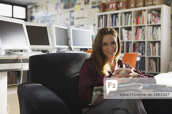 Geschäftsfrau im Büro mit einer Tasse Kaffee  Porträt