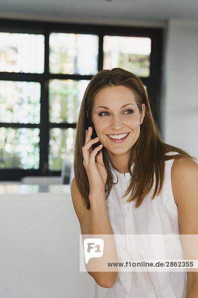 Junge Frau im Büro mit Handy  lächelnd  Portrait