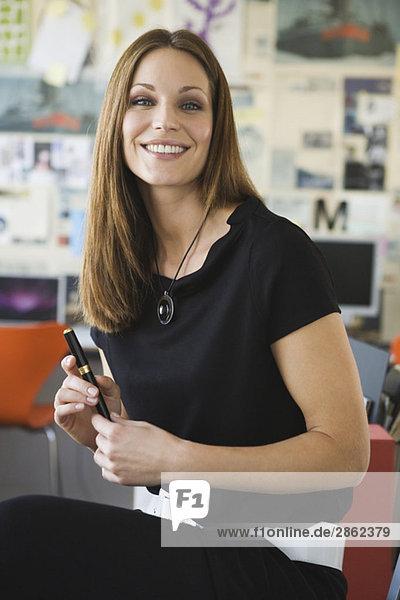 Geschäftsfrau im Büro mit Kugelschreiber  Portrait