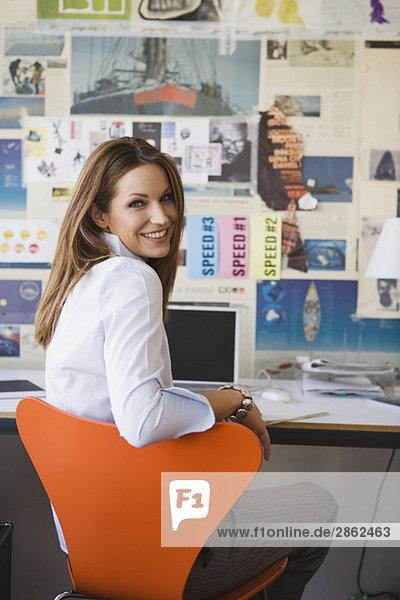 Geschäftsfrau im Büro am Schreibtisch sitzend  lächelnd