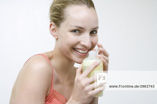 Junge Frau hält Flasche mit Badelotion  Portrait