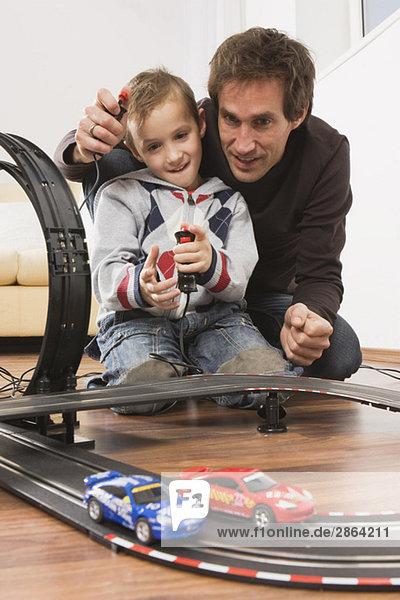 Vater und Sohn (4-5) spielen mit der Spielzeug-Rennbahn