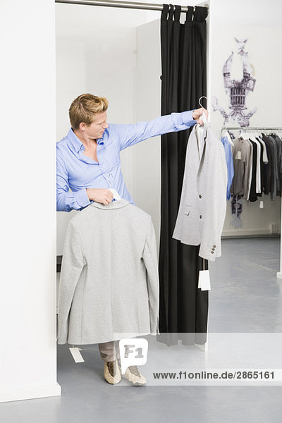 Young man in changing room  holding jackets